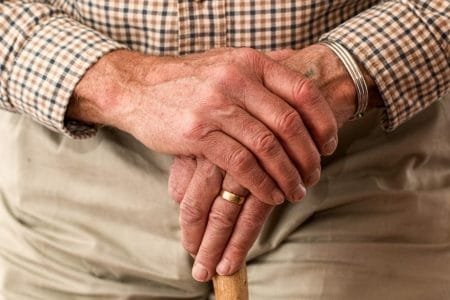 elderly man resting his hand on his cane