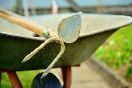 garden hoe laying in a wheelbarrow