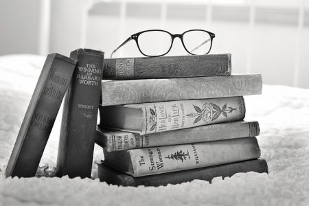 stack of books and a oair of reading glasses