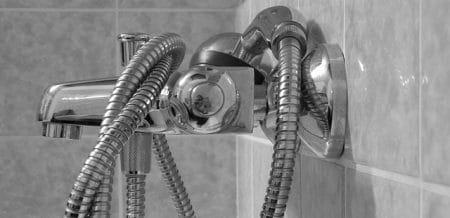 shower head tangled up in a bath tub