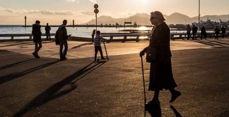 woman walking with cane at beach