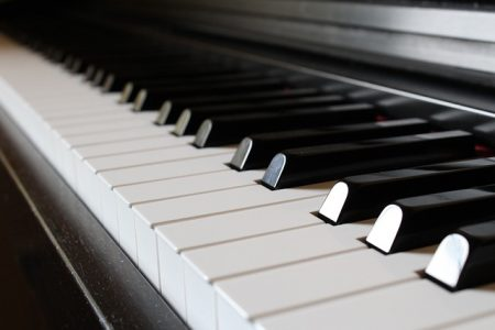 Close up of black and white piano keys on a black piano